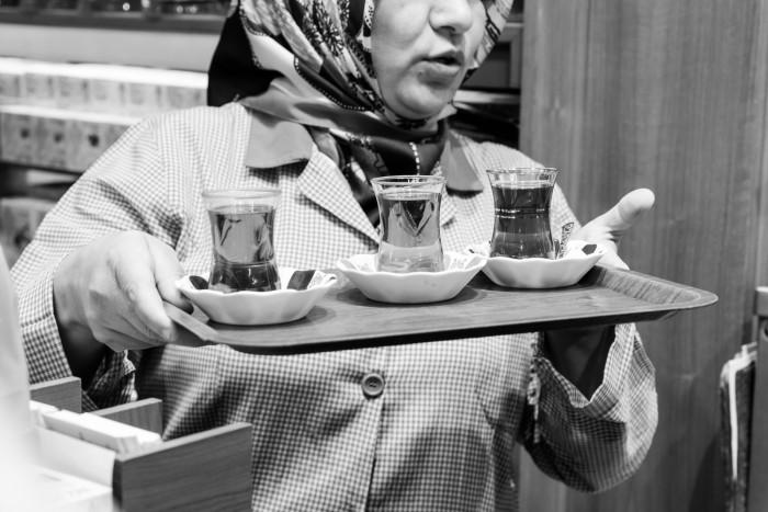 Woman serving tea in the Spice Bazaar, Istanbul Turkey