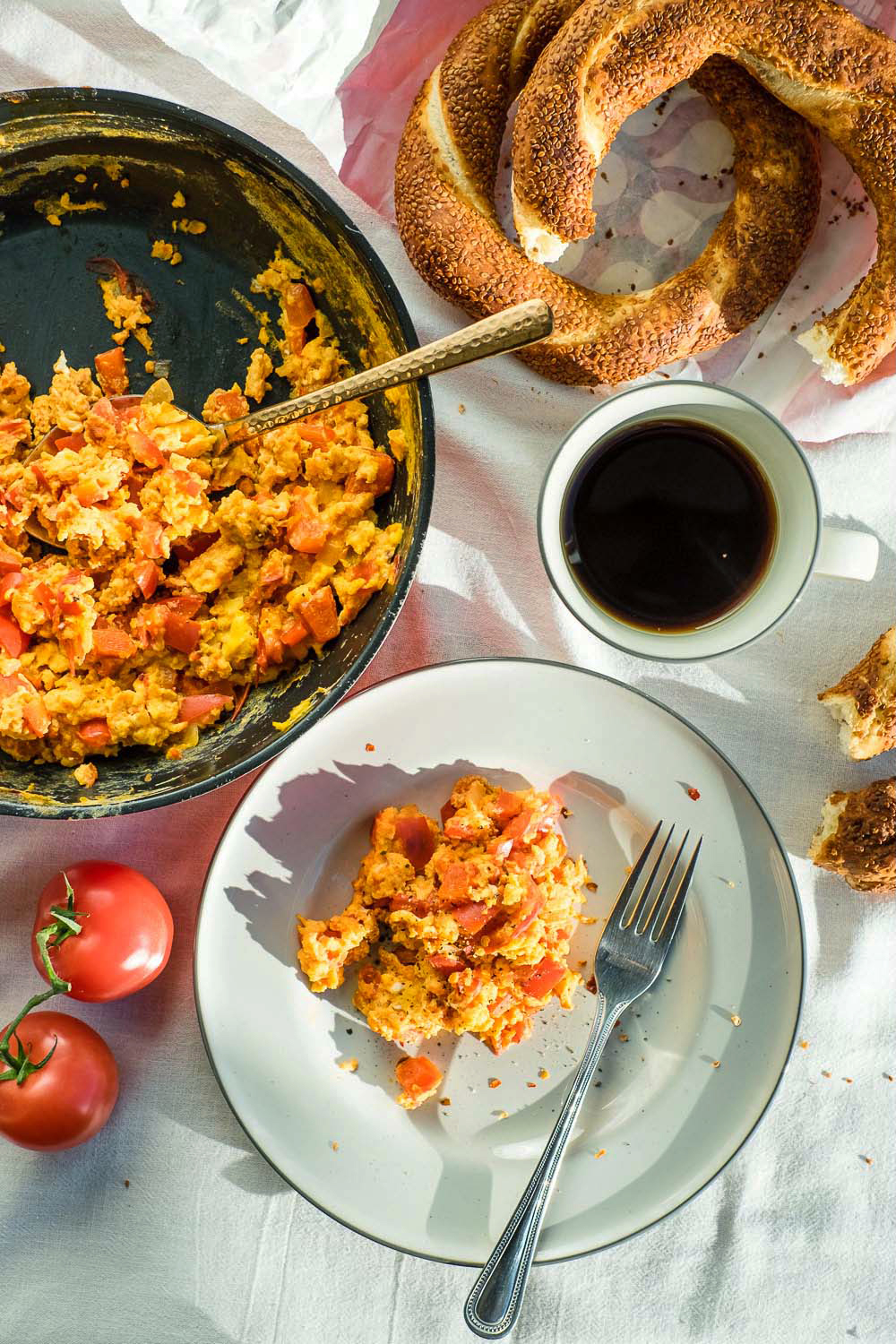 """Menemen is a traditional Turkish dish of eggs scrambled with tomatoes, peppers, and spices such as ground black pepper and chilli, cooked in olive oil. It is often served with """"simit"""" style bread."""