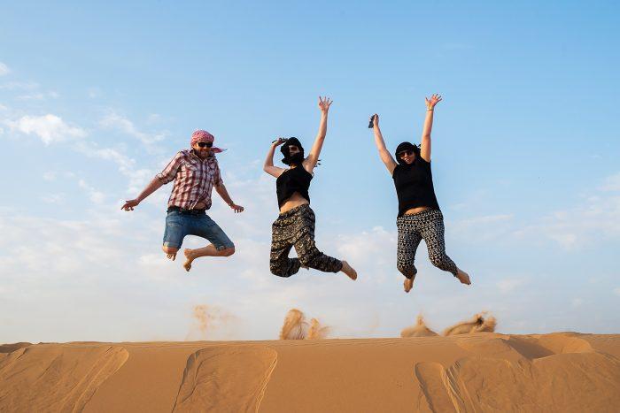 Jumping on sand dunes in Dubai, UAE