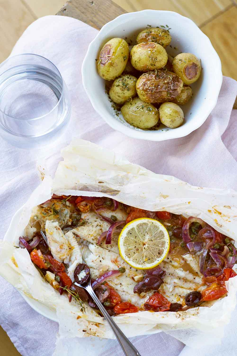 "Sole 'en Papillote' with Tomatoes, Olives, Capers Over the last month, and the arrival of shorter and colder days, I have spent more time cooking at home than I have done in the whole summer. I crave warm food, filling dishes of fish (we don't cook meat at home), spiced pulses and roasted vegetables. The Dover Sole ""en papillote"" is a filling dish, yet light, perfect for a weekday dinner. 70% of fish consumption in the UK comes from just five fishes: Cod, Haddock, Salmon, Tuna and Prawns. Most people don't feel confident cooking with a fish they have never cooked before, so they prefer to stick to the most familiar species. Obviously, this is not sustainable as it leads to over-fishing. In order to promote customers to try different species of fish and seafood, Sainsbury's have launched a new fresh fish range called Fishmonger's Choice. It includes lesser-known fresh British species such as Whiting, Monkfish and Dover Sole, all wild-caught off the South West coast of Britain. The range varies according to the seasons and when a certain species is more abundant in the sea. When I'm baking, I like to experiment with a new recipe every time, but when it comes to cooking I'm a creature of habit. So when Sainsbury's challenged me to cook with Dover sole, at first I was worried about the outcome. I shouldn't have been though, as sole is not a complicated fish to cook. I absolutely love this recipe and I am surely going to make it a lot over the winter. Baking soles en En Papillote is simple and quick. It's a style of baking fish or meat wrapped in a paper parcel, with your favourite vegetables and a dollop of butter. The heat creates steam, which is wrapped inside the parcel and gently cooks the fish. I paired the Dover sole with fresh flavours of the Mediterranean: olives, tomatoes, capers, lemon, thyme and extra virgin olive oil. These flavours remind me of home. This recipe is versatile: you can choose different types of vegetables to cook with the fish (as long as they cook within 15 minutes, such as courgettes or asparagus). I also like to add cooked couscous to the bottom of the parcel, underneath the fish. My husband doesn't love eating fish, but when I prepared this dish for him, he absolutely loved it. Perfect for picky eaters! Ingredients Serves two. • 2 Fishmonger's Choice Dover Sole on the Bone (about 400g in total) • 2 tbsp extra virgin olive oil • 1 small red onion, sliced • 2 cloves garlic, thinly sliced • ½ tsp chilli flakes • 20 cherry tomatoes, halved • 10 large, pitted black olives, halved • 3 tsp capers, drained • 20g unsalted butter, divided in two pieces • 10 fresh thyme sprigs • 2 thin lemon slices • Salt and freshly ground black pepper Preparation Preheat oven to 200°C. Cut two 40cm-long pieces of baking paper. Fold in half, then cut a half-circle or heart-shape. Open flat and place on a baking sheet. Place each sole on a piece of paper. Place a small pan over medium heat. Sauté sliced onions, garlic and chilli flakes in olive oil until golden, for about one minute. Lower the heat. Add the tomatoes, olives, capers Remove skillet from heat; stir in tomatoes, capers and olives. Season with salt and pepper. Cook for a couple of minutes, then remove from the heat. Sprinkle the fish with salt and pepper, then divide the tomato mixture between the two portions. Cover the fish with the vegetables, then top with butter, thyme sprigs and lemon. Lift the other half of baking paper and place over fish. Seal the edges, making small folds all the way around until completely sealed. Place packets on a large baking sheet. Bake in the oven for 15 minutes. Serve the sole in the paper parcel with roasted potatoes on the side. Sainsbury's Fishmonger Choice range is available to buy in over 200 stores nationwide. Disclaimer: this post was written in collaboration with Sainsbury's. All opinions are my own."