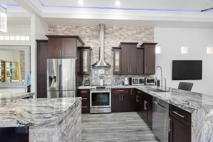Modern kitchen with wooden cabinets, silver appliances and grey marble counters in Coral Springs, United States.