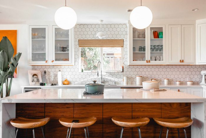 Minimalist Kitchen: white tiles, marble counter, wooden furniture and stools. Copyright @creatveight