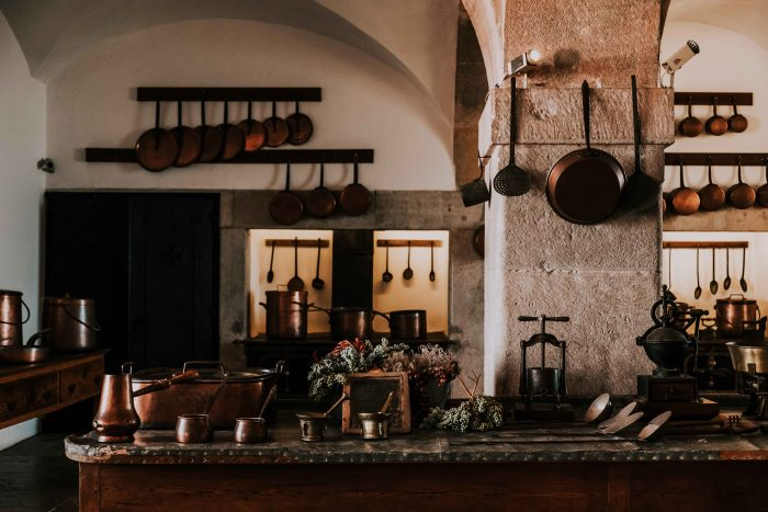 Old style, rustic kitchen design with stone walls and copper pans
