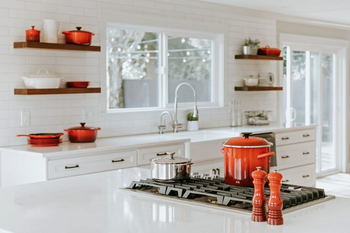 White kitchen design with red Le Creuset casserole pans