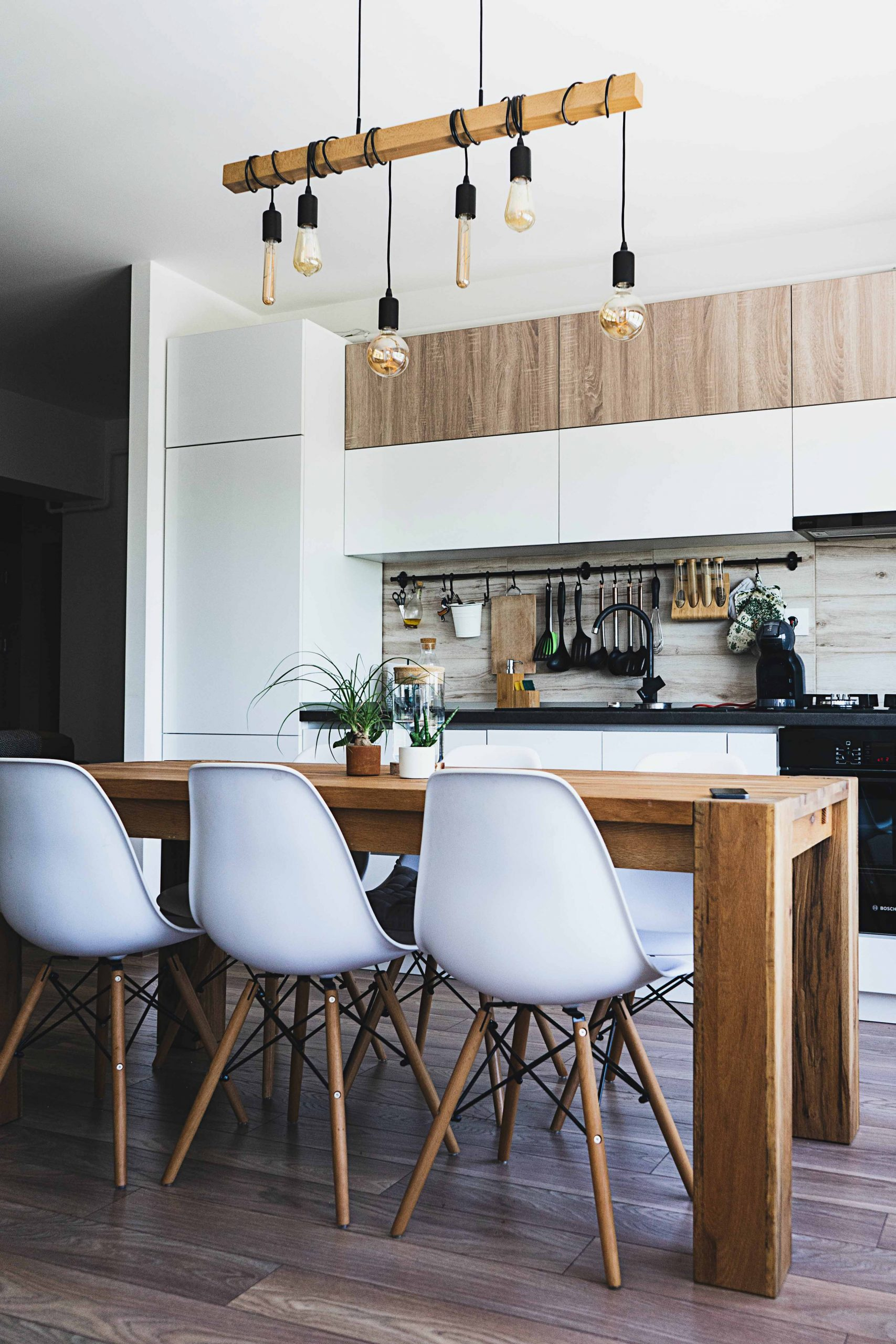 Kitchen design with white cabinets, white Eames chairs, light wooden table, industrial light pendants