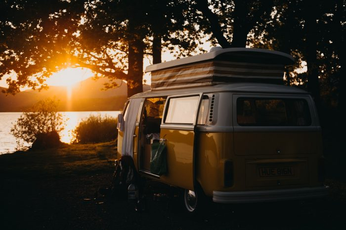 A VW campervan parked by a lake in Scotland at sunset