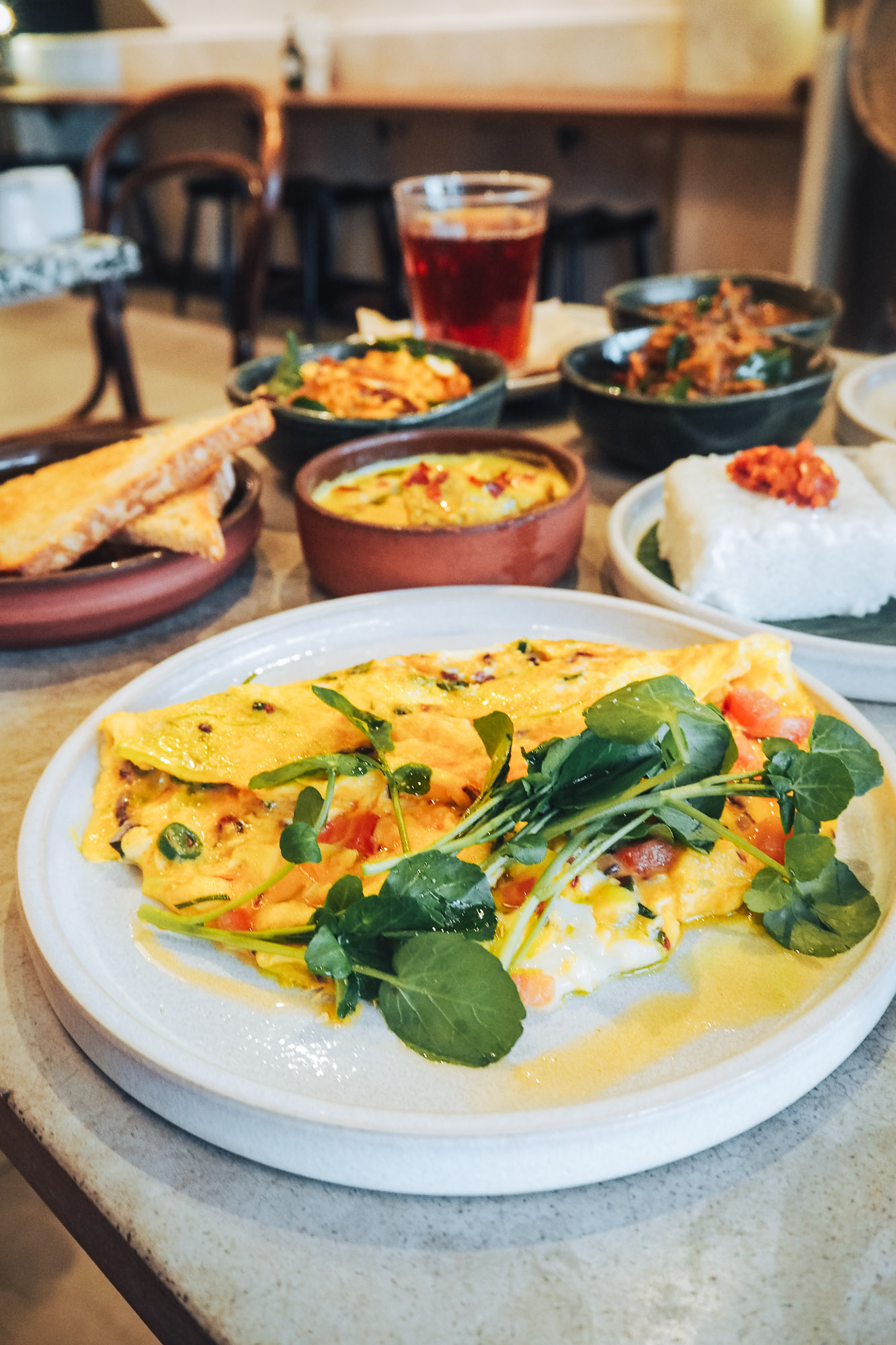 Sri Lankan omelette with sourdough toast and an array of sides for brunch at Kolamba in Soho, London