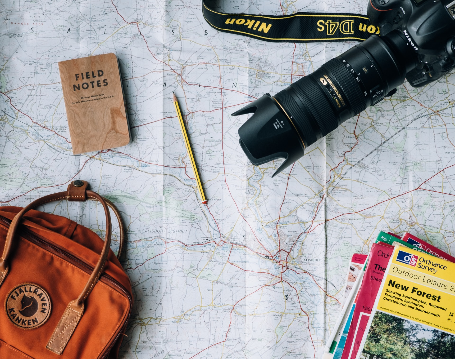 Flat lay photography of Nikon camera, book and backpack