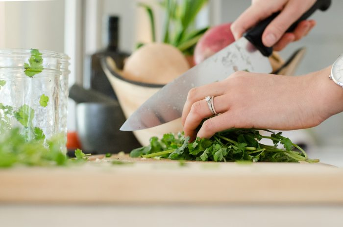 Woman chopping fresh herbs with a Chef's knife