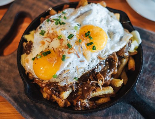 Canadian poutine is a dish of french fries and cheese curds topped with a brown gravy.