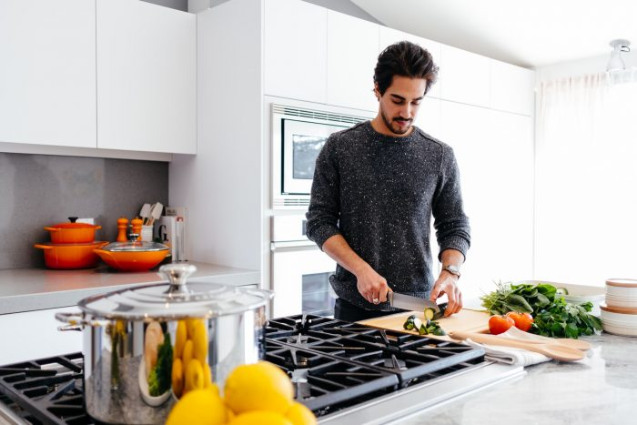 Man chopping vegetables at a kitchen counter