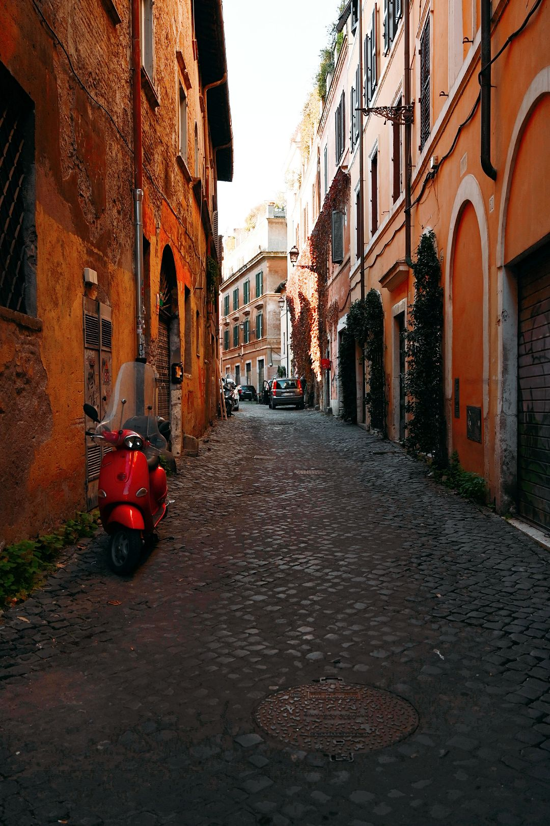 Red scooter in Trastevere neighbourhood in Rome Italy