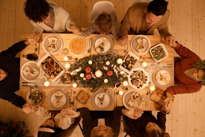 Family sitting at the dinner table praying together