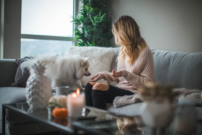 Woman sitting in a cosy living room with dog